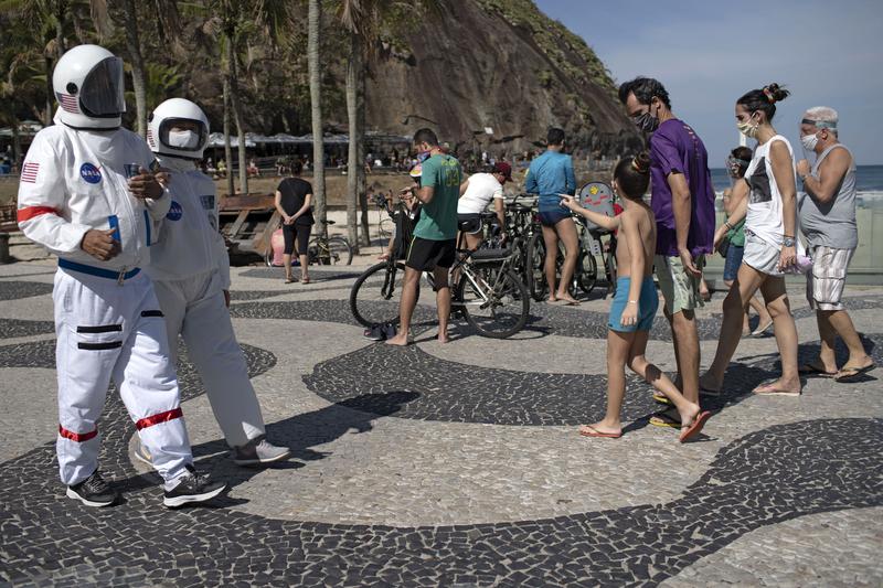 O contador Tercio Galdino e sua esposa Alicea Galdino caminham na Praia do Leme. Tércio que tem problemas crônicos no pulmão desenvolveu manualmente roupas de segurança. Foto: Mauro Pimentel/ AFP